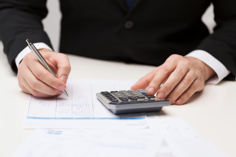 7644052-close-up-of-businessman-with-papers-and-calculator